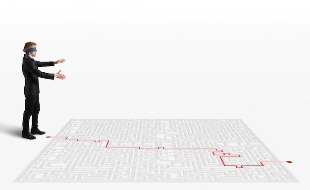 Renderowanie 3d ręka rysuje i pomaga biznesmenowi z zasłoniętymi oczami wydostać się z labiryntu