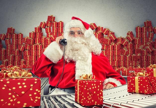 Renderowanie 3d święty mikołaj otrzymuje prośby przez telefon, siedząc na krześle i sprawdzając świąteczne pudełka z prezentami i pakując je na rolce przenośnika