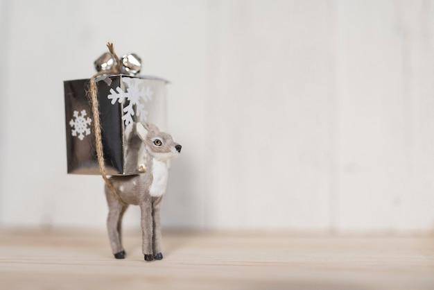 Renifer trzyma prezent na boże narodzenie i kopia przestrzeń