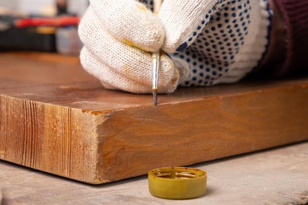 Renowacja drzwi drewnianych, eliminacja ubytków wiórów zbliżenie pędzlem.