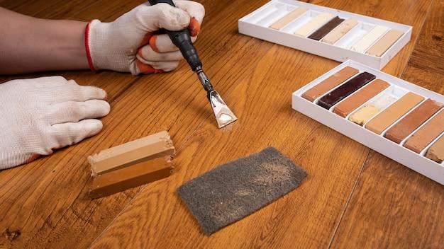 Renowacja laminatu za pomocą wosku, konserwator maskuje uszkodzenia podłogi.