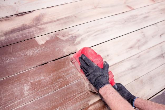 Renowacja mebli za pomocą szlifierki do polerowania powierzchni drewna. szlifowanie podłogi drewnianej za pomocą szlifierki. polerowanie starej podłogi parkietowej za pomocą szlifierki.