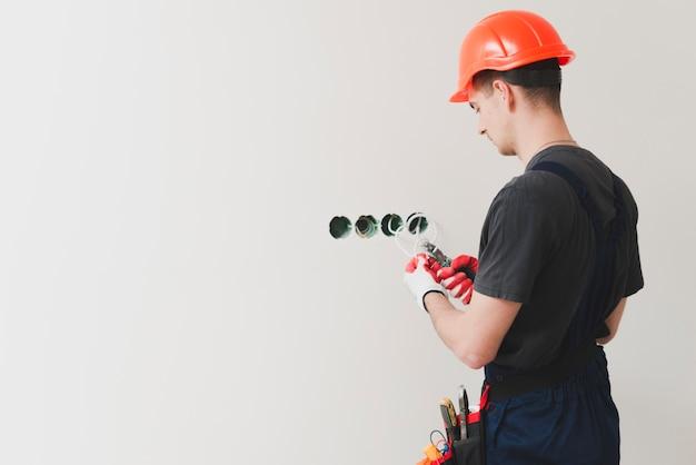 Repairman cięcia kabla na ścianie