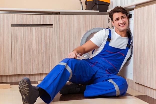 Repairman naprawia pralkę przy kuchnią