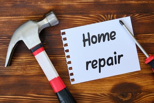 Repairman pracujący narzędzia z majcherem i inskrypcją na nim domowa naprawa na białym drewnianym tle