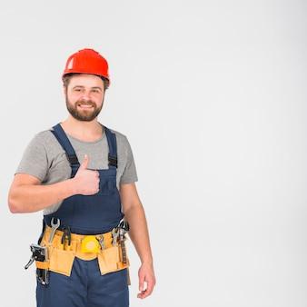 Repairman w kombinezonie i hełm pokazuje kciuk up