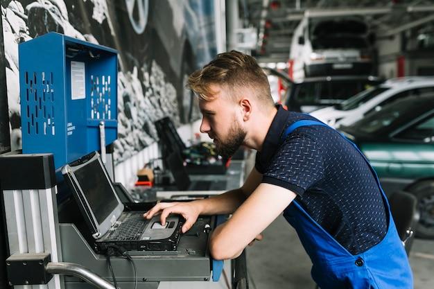 Repairmen używa laptop przy warsztatem