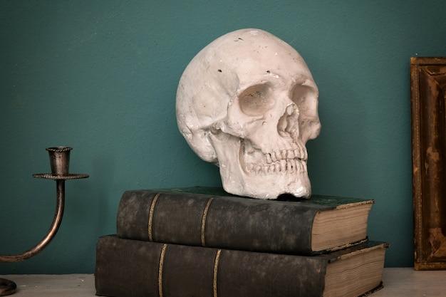 Replika ludzkiej czaszki na dwóch dużych zabytkowych książkach ze skórzanymi grzbietami na zielonej ścianie wewnętrznej