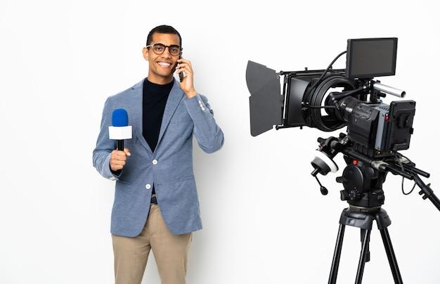 Reporter afroamerykanin mężczyzna trzyma mikrofon i raportuje wiadomości na białym tle, prowadząc z kimś rozmowę z telefonem komórkowym
