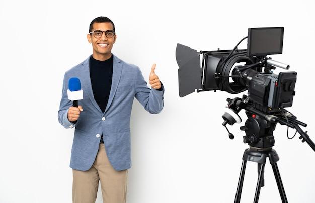 Reporter afroamerykanin mężczyzna trzyma mikrofon i zgłaszanie wiadomości na pojedyncze białym tle, dając kciuk do góry gest