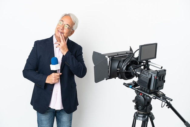 Reporter brazylijczyk w średnim wieku trzymający mikrofon i informujący o wiadomościach na białym tle, patrząc w górę, uśmiechając się