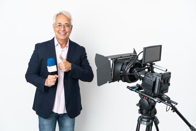 Reporter brazylijczyk w średnim wieku trzymający mikrofon i informujący o wiadomościach na białym tle, pokazujący gest kciuka w górę