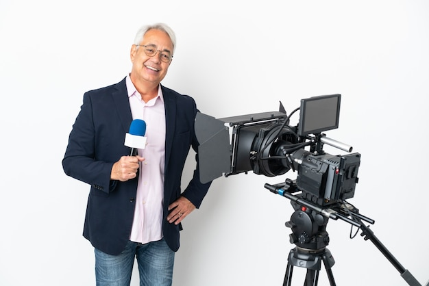 Reporter brazylijczyk w średnim wieku trzymający mikrofon i informujący o wiadomościach na białym tle, pozujący z rękami na biodrach i uśmiechnięty