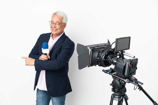 Reporter brazylijczyk w średnim wieku trzymający mikrofon i pokazujący wiadomości na białym tle, wskazując do tyłu