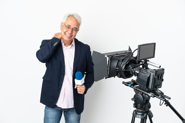 Reporter brazylijczyk w średnim wieku trzymający mikrofon i śmiejący się z wiadomościami na białym tle