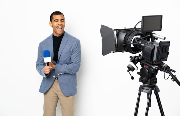 Reporter, człowiek, dzierżący mikrofon i zgłaszający wiadomości na białym tle ściany, dużo się uśmiecha