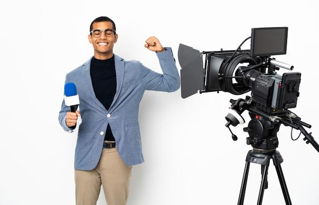 Reporter, człowiek, dzierżący mikrofon i zgłaszający wiadomości na białym tle ściany, robi silny gest