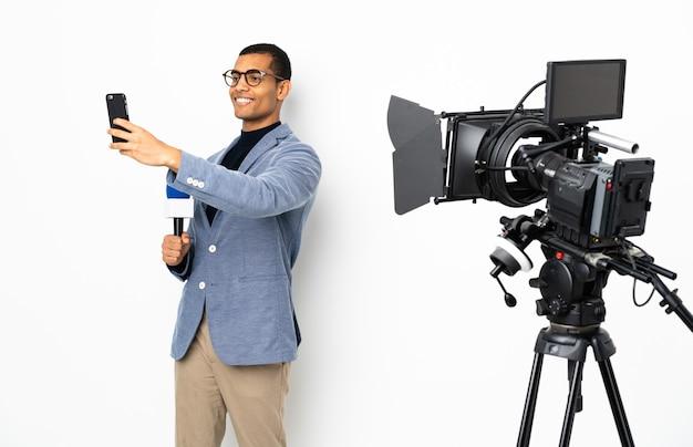 Reporter, człowiek, dzierżący mikrofon i zgłaszający wiadomości nad izolowaną białą ścianą, robiąc selfie