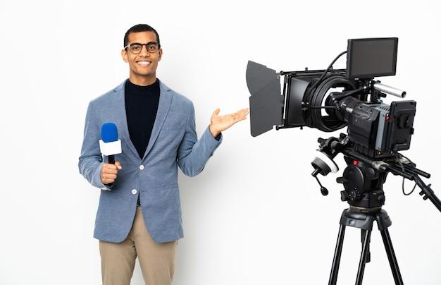 Reporter, człowiek, dzierżący mikrofon i zgłaszający wiadomości, nad izolowaną białą ścianą, trzymający copyspace wyobrażony na dłoni, aby wstawić reklamę