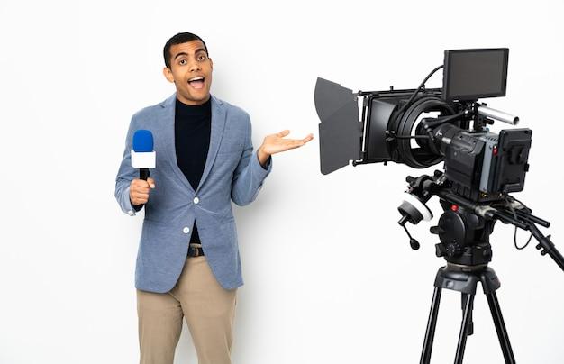 Reporter, człowiek, dzierżący mikrofon i zgłaszający wiadomości nad izolowaną białą ścianą z wyrazem twarzy zszokowany