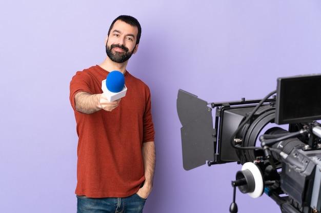 Reporter, człowiek, dzierżący mikrofon i zgłaszający wiadomości nad izolowaną fioletową ścianą