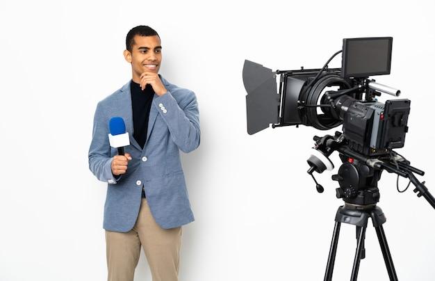 Reporter, człowiek, dzierżawa mikrofon, i, raportowanie, wiadomości, na, odizolowany, biała ściana, patrząc z, bok, i, uśmiechnięty