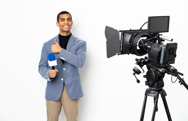 Reporter, człowiek, dzierżawa mikrofon i zgłaszanie wiadomości nad izolowaną białą ścianą, dając kciuk w górę gestem