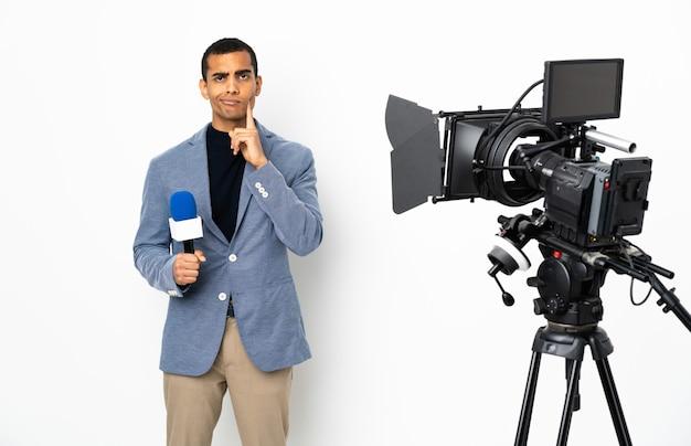 Reporter, człowiek, dzierżawa mikrofon i zgłaszanie wiadomości nad izolowaną białą ścianą i myślenie