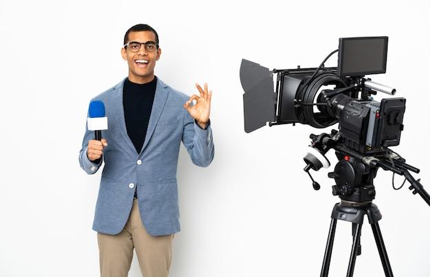 Reporter, człowiek, dzierżawa mikrofon i zgłaszanie wiadomości nad izolowaną białą ścianą, pokazując znak ok obiema rękami