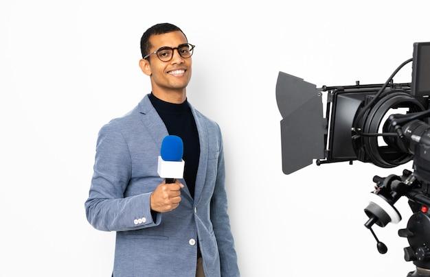 Reporter, człowiek, dzierżawa mikrofon i zgłaszanie wiadomości nad izolowaną białą ścianą