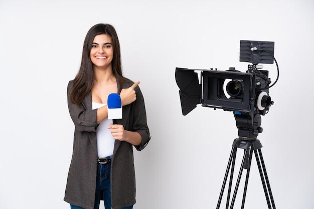 Reporter kobieta trzyma mikrofon i donosi wiadomości na białej ścianie palcem wskazującym na bok
