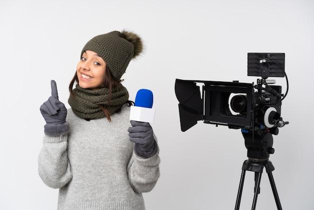 Reporter kobieta trzyma mikrofon i donosi wiadomości na białej ścianie pokazując i podnosząc palec na znak najlepszego