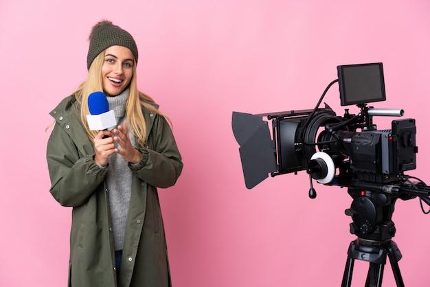 Reporter kobieta trzyma mikrofon i donosi wiadomości na białym tle różowy oklaskuje