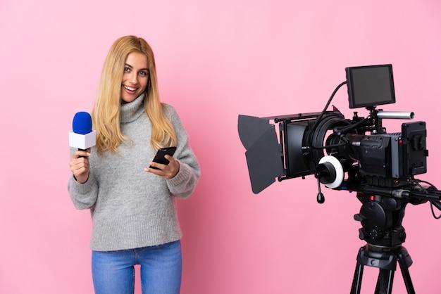 Reporter kobieta trzyma mikrofon i donosi wiadomości na różowej ścianie, wysyłając wiadomość za pomocą telefonu komórkowego