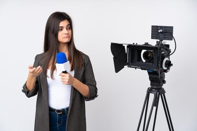 Reporter kobieta trzyma mikrofon i donosi wiadomości nad biel ścianą