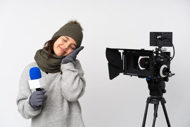 Reporter kobieta trzyma mikrofon i donosi wiadomości nad odosobnioną biel ścianą robi sen gestowi w dorable wyrażeniu