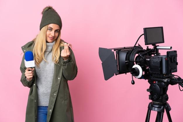 Reporter kobieta trzyma mikrofon i donosi wiadomości nad odosobnioną menchii ścianą robi pieniądze gestowi