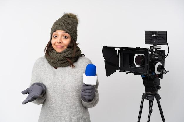 Reporter kobieta trzyma mikrofon i donosi wiadomości nad odosobnionym biel ściany ono uśmiecha się