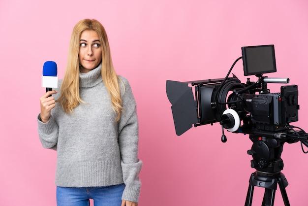 Reporter kobieta trzyma mikrofon i donosi wiadomości nad odosobnionym menchiami ma wątpliwości podczas gdy przyglądający up