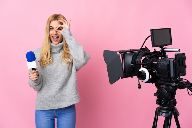 Reporter kobieta trzyma mikrofon i donosi wiadomości nad różową ścianą pokazuje ok znaka z palcami