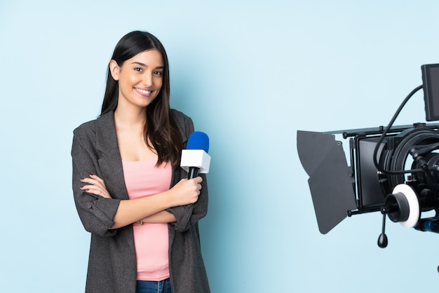 Reporter kobieta trzyma mikrofon i donosi wiadomości odizolowywających na błękicie