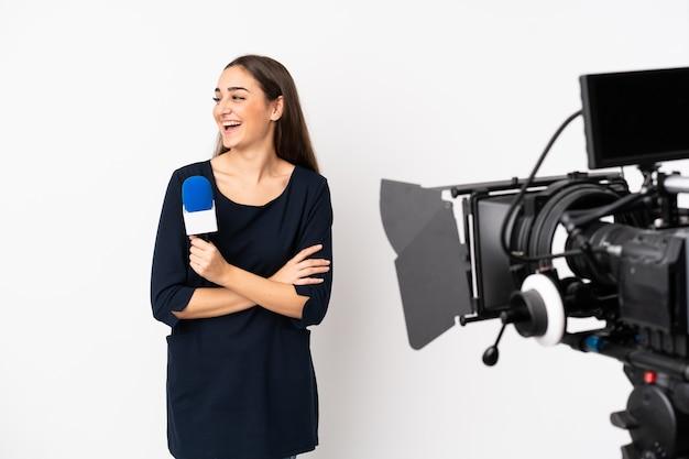 Reporter kobieta trzyma mikrofon i raportowanie wiadomości na białej ścianie szczęśliwa i uśmiechnięta