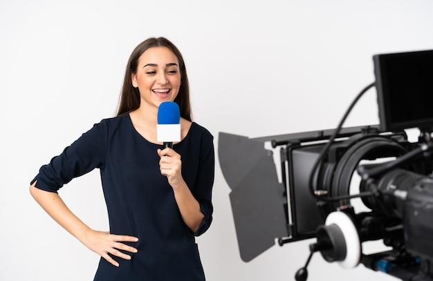 Reporter kobieta trzyma mikrofon i raportowanie wiadomości na białym tle na białej ścianie