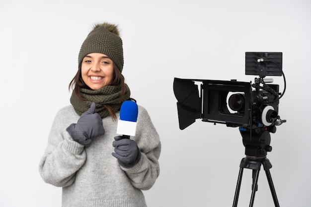 Reporter kobieta trzyma mikrofon i raportuje wiadomości na na białym tle, dając kciuk w górę gest