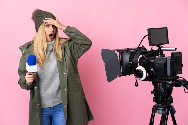 Reporter kobieta trzyma mikrofon i raportuje wiadomości nad różową ścianą robi niespodzianka gestowi podczas gdy patrzejący przód