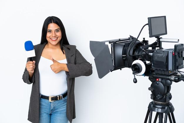 Reporter kolumbijska kobieta trzyma mikrofon i donosi wiadomości na bielu