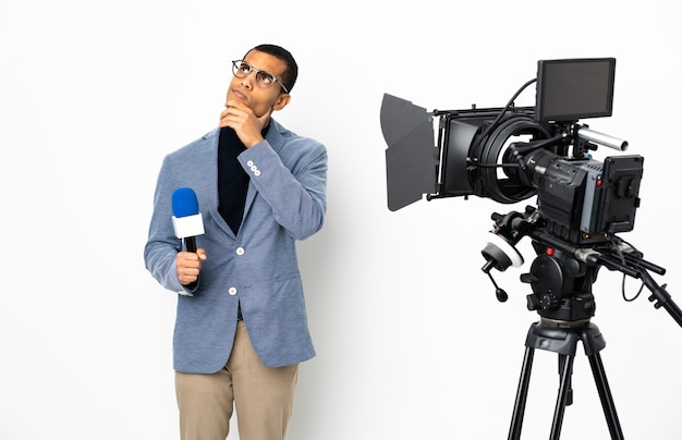 Reporter, który trzyma mikrofon i przekazuje wiadomości na białym tle ściany, mając wątpliwości