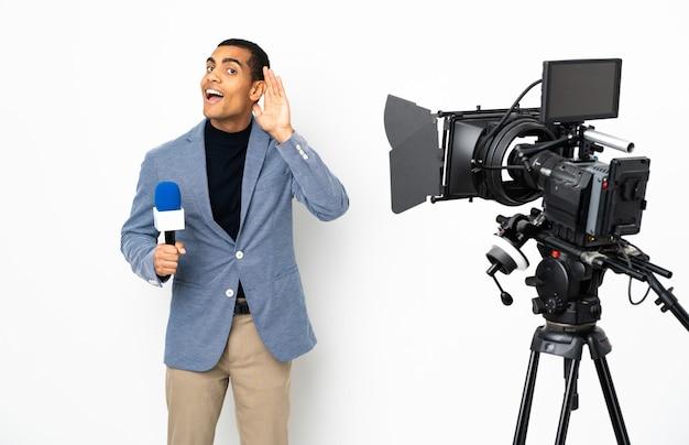 Reporter mężczyzna trzyma mikrofon i zgłasza wiadomości na izolowanej białej ścianie, słuchając czegoś, kładąc rękę na uchu