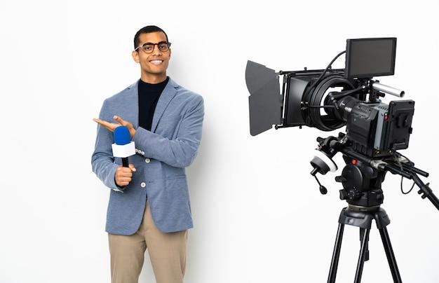 Reporter mężczyzna trzymający mikrofon i zgłaszający wiadomości nad izolowaną białą ścianą przedstawiający pomysł, patrząc w kierunku uśmiechniętym