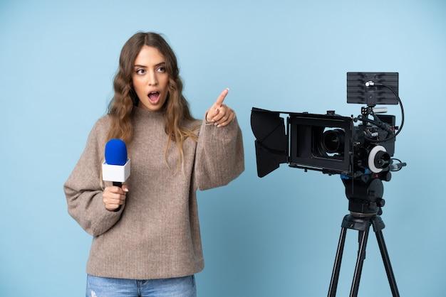 Reporter młoda kobieta trzyma mikrofon i donosi wiadomości wskazuje daleko od
